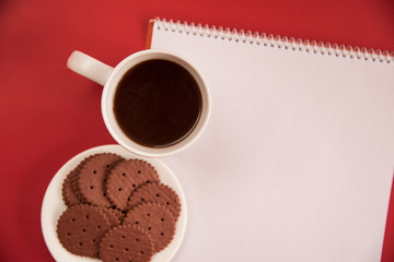 A white Cup of tea, notebook and Chocolate cookies stands on a white background. copy space, flat lay.