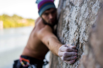 Portrait man cliff climber is climbing a rock.