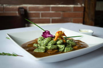 Spinach gnocchi with red sauce served with flowers on a white and rustic background