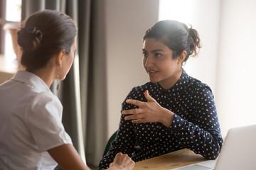 Serious indian mentor worker talk to female colleague teach intern