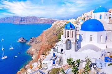 Piękny miasteczko Oia na wyspie Santorini, Grecja. Tradycyjna biała architektura i greccy ortodoksyjni kościół z błękitnymi kopułami nad kalderą w morzu egejskim, Grecja. Malownicze tło podróży.