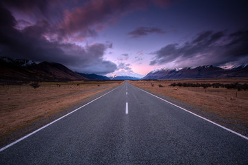 Journey to the Hooker Valley, South Island New Zealand, view during sunset on the middle of the road with snow cap mountain.