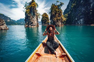 szczęśliwa młoda kobieta turysta w azjatyckim kapeluszu na łodzi na jeziorze