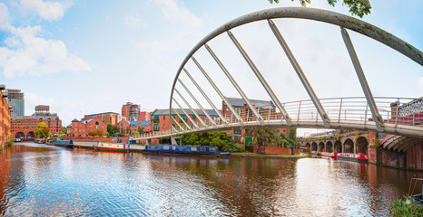 Waterway canal area with a narrowboat on the foreground modern bridge, Castlefield district