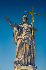 Statue of saint with cross at the Charles Bridge in Prague at bl
