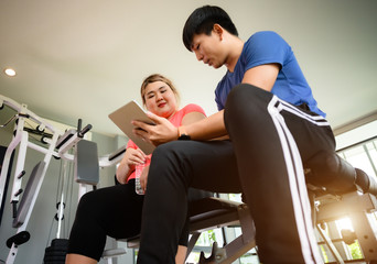 fat plump woman learning health report from the exercise record in device with suggestion by personal trainer or coach