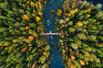 Widok z lotu ptaka na szybki przepływ rzeki przez skały i kolorowy las. Jesień w Finlandii