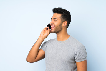 Young handsome man over isolated background keeping a conversation with the mobile phone with someone