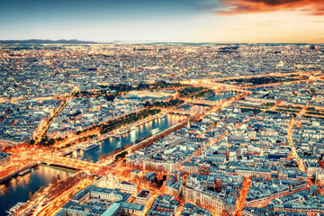 Paris city skyline rooftop view with River Seine at night, France. Evening panorama.