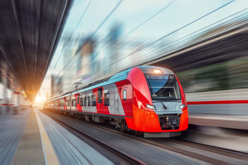 Elektryczny pociąg pasażerski jedzie z dużą prędkością wśród krajobrazu miejskiego.