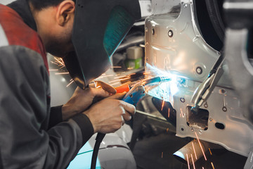 Industrial worker at car service welds automotive body. Metalworking with carbon dioxide welding.