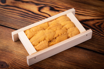 raw sashimi japanese sea urchin in wooden pallet