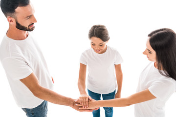overhead view of smiling family putting hands together isolated on white