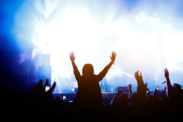 Silhouette of crowd concert, music fans on show. Raised hands and smartphones