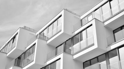 Fragment elewacji budynku z oknami i balkonami. Nowoczesny dom z wieloma mieszkaniami. Czarny i biały.