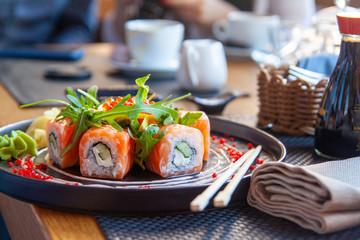 Sushi roll japońskie jedzenie w restauracji. Zestaw California Sushi Roll z łososiem, warzywami, ikrą. Sushi z pałeczkami. Japońskie menu restauracji