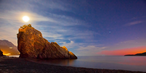 Night landscape, a dark blue nest with stars, a red streak of evening dawn and a huge cloaked cliff by the sea, behind the cliff a full bright moon shines.