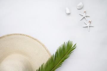 Flat lay de sombrero de playa, piedras y palmera