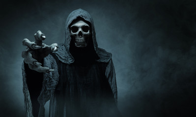 Grim reaper reaching towards the camera over dark background with copy space