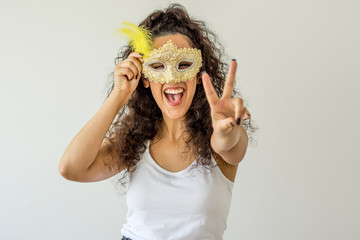 Young woman smiling holding carnival mask on white background