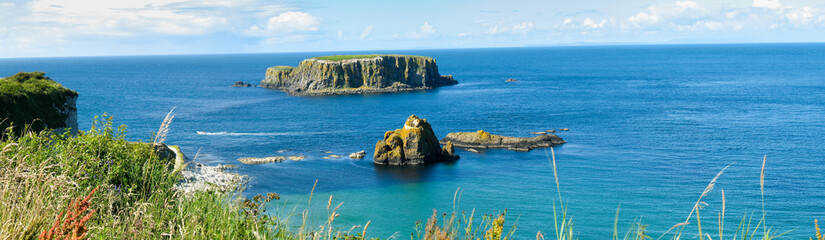 Panoramic view of Rocky islands on the turquoise ocean, cliffs of Northern Ireland
