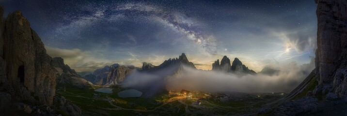 Beautiful panoramic shot of a mountain valley with a small illuminated house under the starry sky