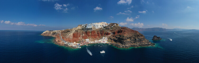 Aerial drone panoramic photo of traditional and picturesque village of Oia in volcanic island of Santorini, Cyclades, Greece