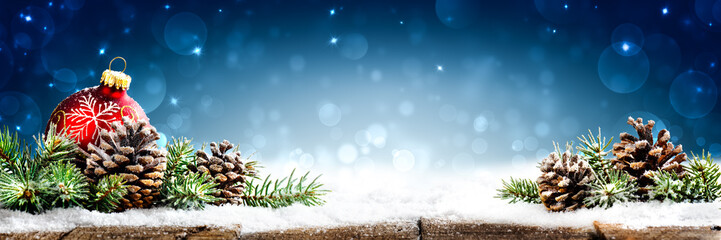 Christmas - Banner Of Red Ornament, Pine-cones And Branches On Snowy Wooden Table With Blue Bokeh Background