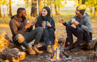 Friends sitting beside fireplace in autumn forest, enjoying time together