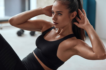 Slim fitness female in gym pumping press. Sweating strong fitnesswoman