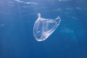 Plastic bag floating in the blue sea water. World ocean contaminated by  plastic. Environment pollution concept.