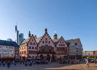 Outdoor sunny view of old town at Römerplatz, historical market square, surrounded with Römerberg, timber medieval German house, and city hall in Frankfurt, Germany.