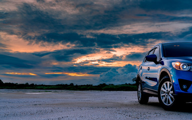 Luxury blue SUV car parked on land beside tropical forest with beautiful sunrise sky. New car with sport and modern design. Car drive for adventure road trip. Nature landscape. Automotive industry.