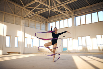 Active beautiful rhythmic gymnast standing in Sur le cou-de-pied pose, waving long colourful ribbon in the air, dancing in bright sports hall, professional sport concept