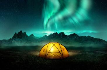 Świecący żółty namiot kempingowy pod piękną zieloną zorzą polarną. Podróży przygoda krajobraz tło. Kompozyt fotograficzny.