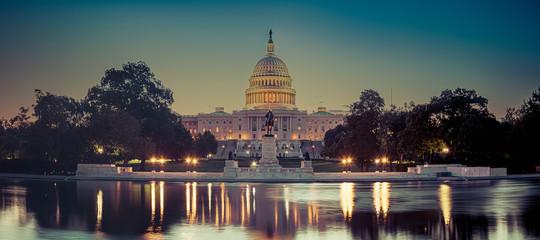 Panoramiczny obraz Kapitolu Stanów Zjednoczonych z kapitolu odbijającego basen w świetle poranka.