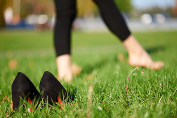 Black shoes in the grass on a background of barefoot female legs.