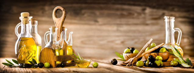 Fresh olives in rustic bowls on old wooden table. Virgin olive oil in clear glass bottles copy space.  Panorama or banner concept.