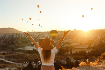 Beautiful young attractive girl in a hat stands on the mountain with flying air balloons on the background. Girl in the sunrise. View from the back. Famous tourist Turkish region Cappadocia.