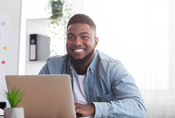 Portrait of smiling african employee at workplace in modern office
