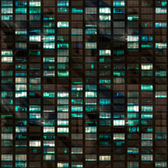 .265/5000.Building facade at night with some windows illuminated and some not. Urban night detail.