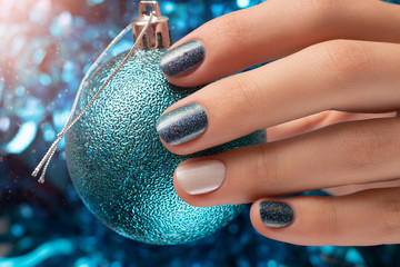 Beautiful female hand with blue christmas nail design