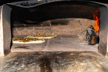 Pizza baking in wood fire oven