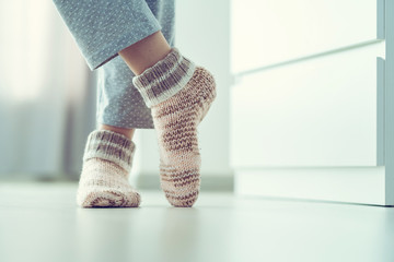 Woman in pajamas and cozy soft warm knitted winter socks at home
