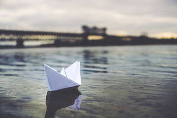 Paper boat floats in the river
