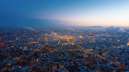 Beautiful aerial view to Moscow city on the sunset. Picturesque motion of the evening metropolis with street and building lights gradually turning on and colorful sky on the background.
