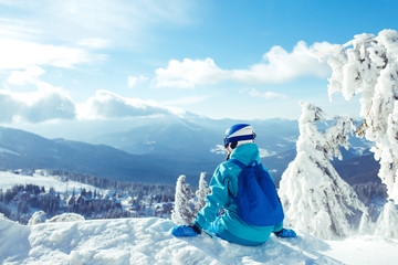A young girl enjoys beauty of winter landscape. A beautiful girl in winter clothes, a blue helmet and jacket is having a great time in the mountains. Concept of travel, leisure, freedom, sport, nature