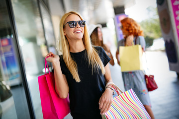 Shopping, fun and tourism concept. Beautiful girls with shopping bags in ctiy