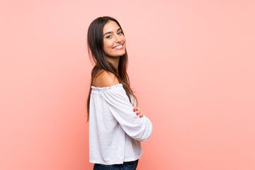 Young woman over isolated pink background with arms crossed and looking forward
