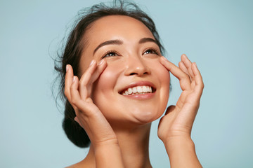 Skin care. Woman with beauty face touching healthy facial skin portrait. Beautiful smiling asian girl model with natural makeup touching glowing hydrated skin on blue background closeup
